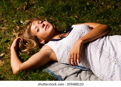 blonde teenage girl lying on the grass