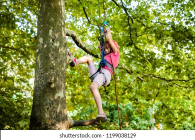 Blonde teenager girl in red helmet and pink clothes climbing on the tree with ropes