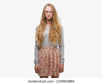 Blonde teenager woman wearing flowers skirt skeptic and nervous, frowning upset because of problem. Negative person.