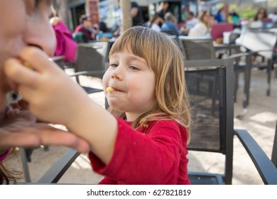 blonde three years old child, with red shirt, feeding mother with cheese puff, sitting in terrace exterior bar cafe with grey chair