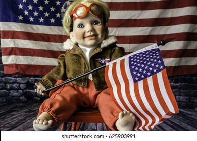 blonde toddler doll with red goggles and jacket sitting on red rocking chair in bare feet holding American flag with large American flag background