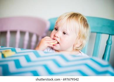 Blonde toddler girl eating fresh healthy fruit
