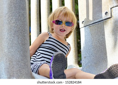 A blonde toddler girl in sun glasses finds a slide in the shade that's not to hot to slide on.