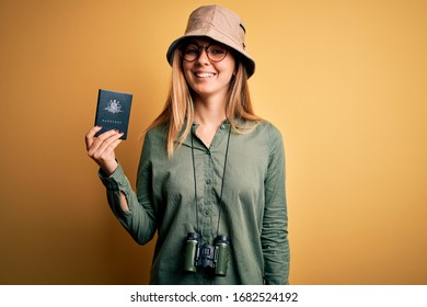Blonde tourist woman with blue eyes on vacation holding australian passport using binoculars with a happy face standing and smiling with a confident smile showing teeth