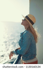 Blonde traveler woman in hat daydreaming on cruise ship