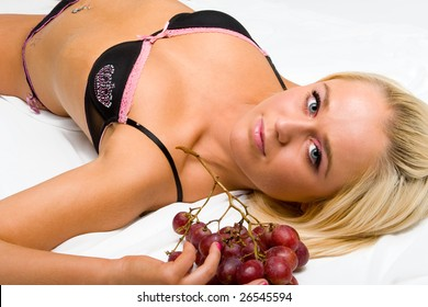 blonde in underwear lays on the white with grapes