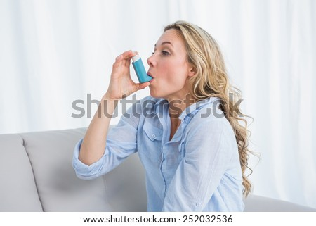 Blonde using her asthma inhaler on stock photo edit now