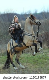Blonde Viking warrior woman riding a horse with ax in hand. Scandinavian warrior woman in forest with war makeup, ready to attack