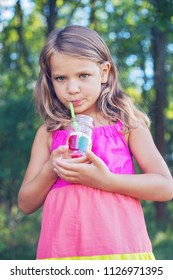 Blonde wavy haired little girl sipping lemonade from a jar