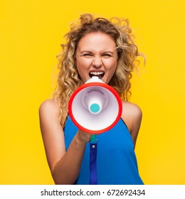 Blonde wavy haired woman wearing blue top yelling with loudspeaker standing against yellow background.