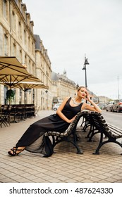 Blonde wearing a black gown leans on a city bench.