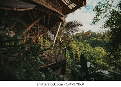 Blonde in white dress on balcony of a bamboo eco house in the jungle. eco tourism in Bali - island of gods. tropical forest. green village. Ubud style.