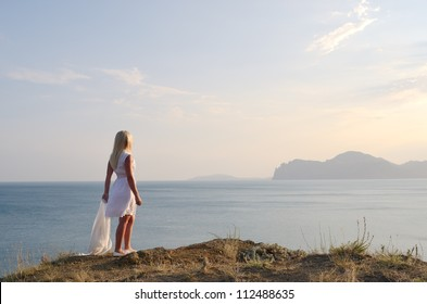 Blonde in a white dress standing on the mountain and looks at the sea