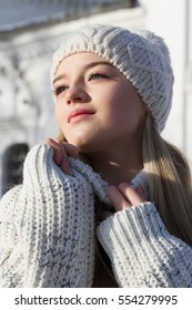 Blonde in white sweater and white knitted cap. Winter portrait