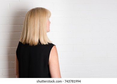 Blonde white woman, dressed in black with back to camera facing a white brick wall background.