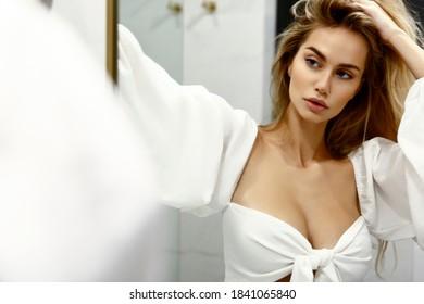 Blonde weiße Frau, die sich im Bad posiert und im Spiegel reflektiert, so hübsch sexy und schlank