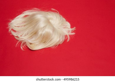 the blonde wig fell on red background. the concept for barbershop.