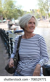 Blonde woman 50 plus navy striped shirt in Amsterdam canals