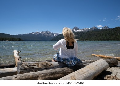 Blonde woman with back facing camera looks out to the Sawtooth Mountains while sitting on logs at Redfish Lake. Wind blows her long hair