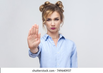 Blonde woman with bad attitude making stop gesture with her palm outward, saying no, expressing denial or restriction. Studio shot