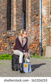Blonde woman with baggage on the historic street.