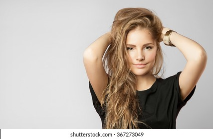 Blonde woman with beautiful curly hair and natural makeup in everyday clothes