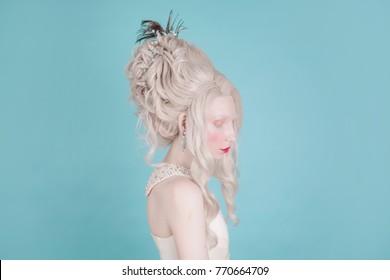 Blonde woman with beautiful luxurious rococo hair style in white dress on a blue background