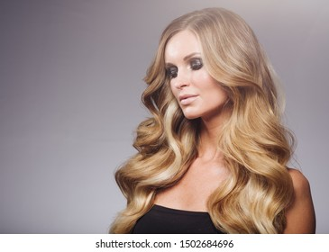 Blonde woman beauty hair curly long hairstyle perfect beauty concept makeup