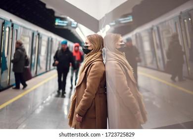 Blonde woman in black medical mask standing in subway near carriage. Coronavirus epidemic.