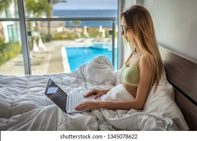 Blonde woman blogger freelance IT works at home on vacation in an apartment overlooking the sea, ocean white bed with a computer. Girl typing on laptop, she does homework on netbook, holiday in hotel