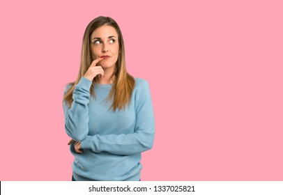 Blonde woman with blue shirt having doubts while looking up on isolated pink background