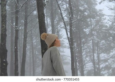 BLONDE WOMAN WITH BRAIDED HAIR, IN SNOW COVERED PINE FOREST
