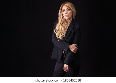 Blonde woman, business woman, middle-aged, European-Portuguese, posing with positive emotions on a black background.