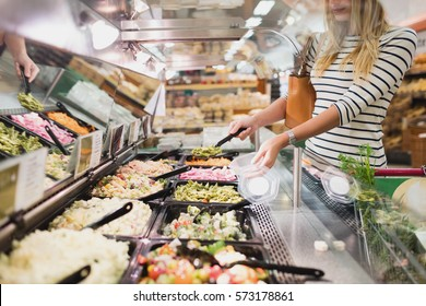 Blonde woman buying pasta prepared meal in grocery store