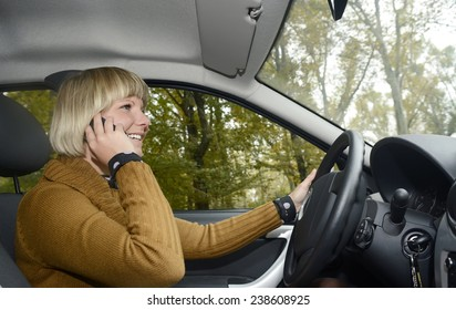 Blonde woman in car using mobile phone