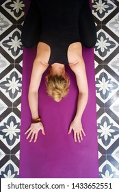Blonde Woman in Child's Pose Asana on  Purple Mat and Black and White Tile Flooring