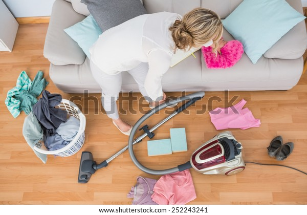 Blonde woman cleaning her chaotic living room at home