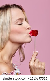 Blonde woman with closed eyes kisses candy. Red female lips shape lollipop. Sweet tooth concept.