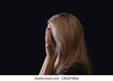 Blonde woman covering her face with palms of her hands, crying, profile photo with dark background