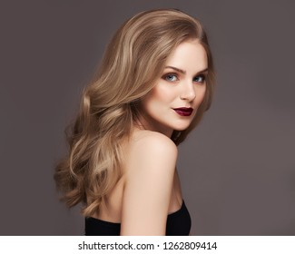 Blonde woman with curly beautiful hair smiling on gray background