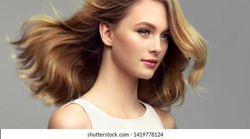 Blonde Frau mit lockig schönen Haaren auf grauem Hintergrund. Das Mädchen mit einem angenehmen Lächeln. Haarschnitt mittlerer Länge. Bob-Frisur