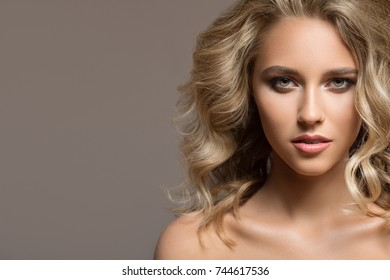 Blonde woman with curly beautiful hair on gray background.