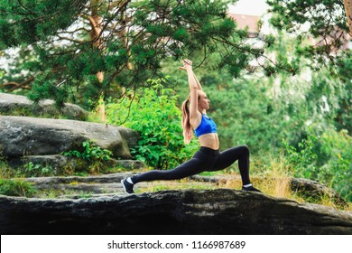 Blonde woman doing anjaneyasana outdoors on a rock in the forest. Yoga nature concept