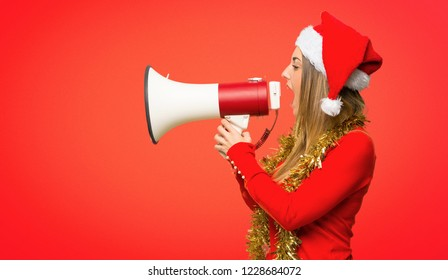 Blonde woman dressed up for christmas holidays shouting through a megaphone to announce something on red background