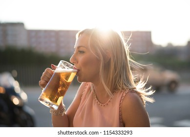 Blonde woman drinking beer in bar with suset light in background