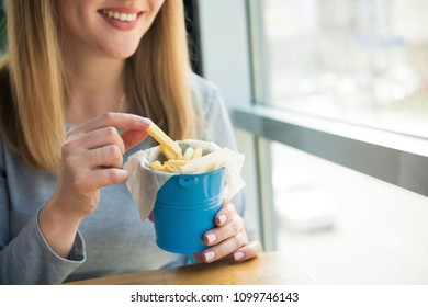 Blonde woman eat fastfood french fries in a cafe. fast lunch