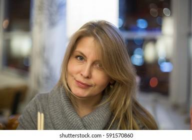 Blonde woman is eating in japanese restaurant
