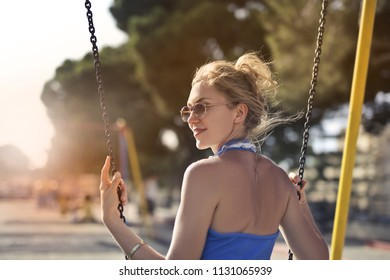 Blonde woman enjoying summertime in a park.