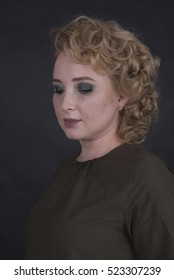 blonde woman with evening makeup on a black background