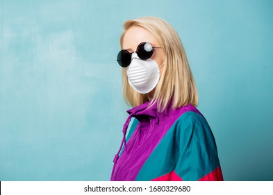Blonde woman in face mask and 90s style clothes on blue background